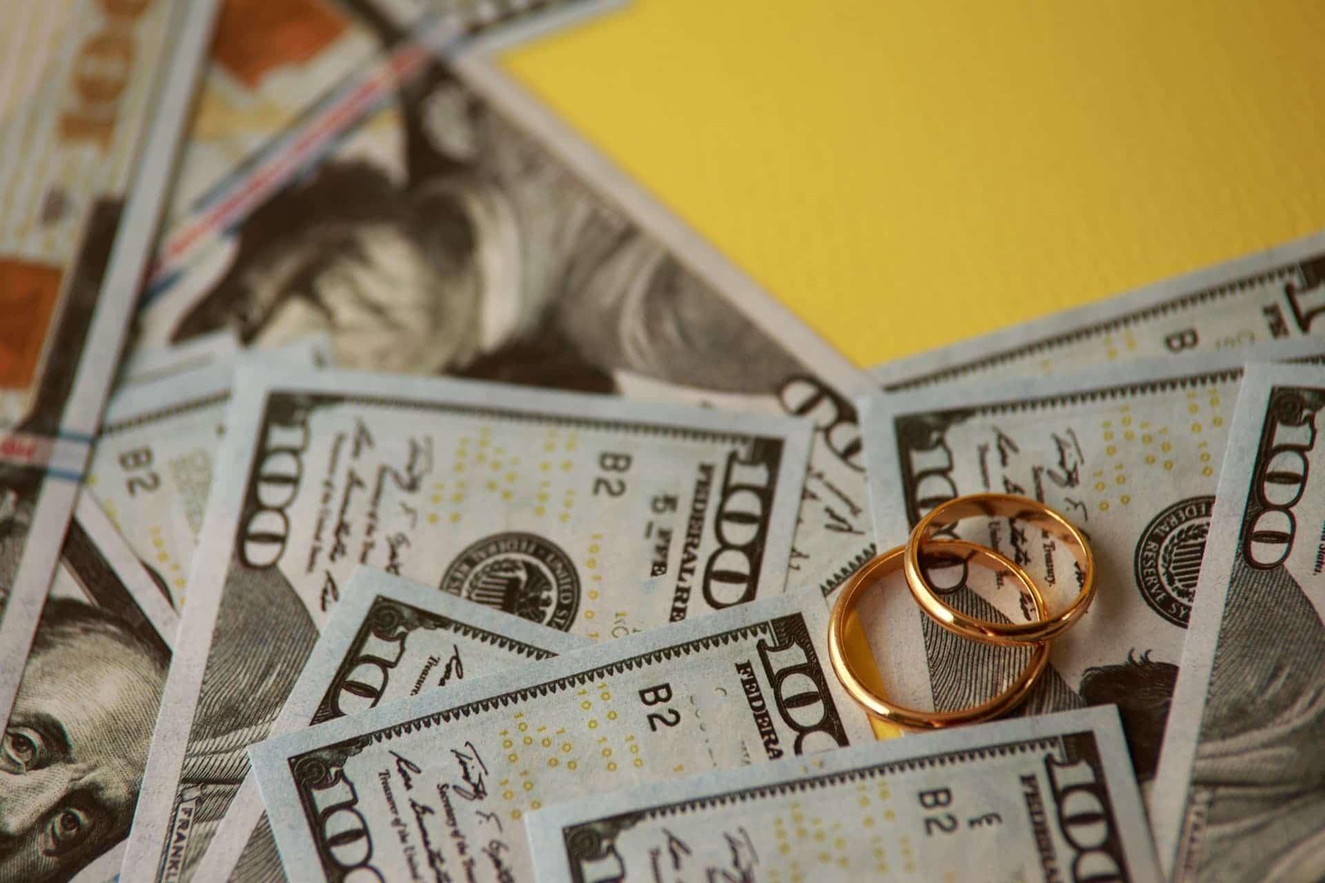 wedding-rings-atop-one-hundred-dollar-bills
